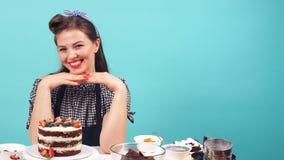 Cuoco unico di pasticceria felice della ragazza che sorride alla macchina fotografica mentre sedendosi alla tavola con pasticceri video d archivio