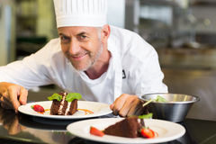 Cuoco unico di pasticceria maschio sorridente con il dessert in cucina Fotografia Stock