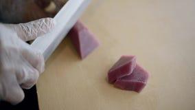 Cuoco unico di sushi che taglia tonno fresco per il sashimi video d archivio