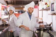 Cuoco unico ed il suo assistente alla cucina dei bistrot Fotografie Stock Libere da Diritti