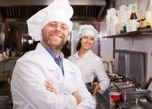 Cuoco unico ed il suo assistente alla cucina dei bistrot Fotografia Stock Libera da Diritti