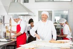 Cuoco unico felice Cutting Ravioli Pasta al contatore dentro Fotografie Stock