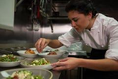 Cuoco unico femminile che guarnisce i piatti dell'aperitivo alla stazione di ordine Fotografia Stock
