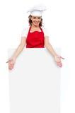 Cuoco unico femminile che propone dietro il tabellone per le affissioni bianco in bianco Immagine Stock Libera da Diritti