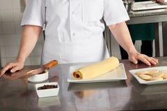Cuoco unico femminile With Chocolate Roll sul contatore Fotografie Stock