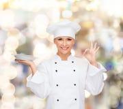 Cuoco unico femminile con il piatto che mostra segno giusto Fotografia Stock Libera da Diritti