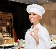 Cuoco unico femminile sorridente che mostra il segno giusto della mano Immagini Stock