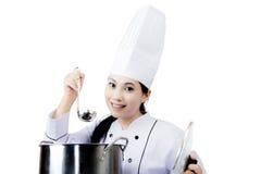 Cuoco unico grazioso che assaggia una minestra sullo studio Fotografia Stock Libera da Diritti