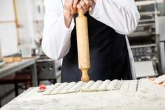 Cuoco unico Holding Rolling Pin While Standing At Counter Fotografie Stock Libere da Diritti