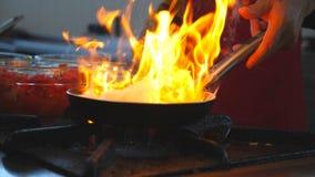 Cuoco unico irriconoscibile che cucina il piatto fiammeggiato di stile sulla pentola nel ristorante dell'hotel Un cuoco maschio c video d archivio