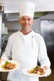 Cuoco unico maschio di Sonfident con cibo cotto in cucina fotografia stock