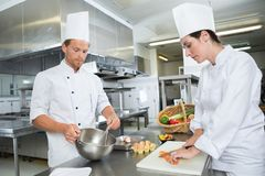 Cuoco unico maschio e femminile che posa nella cucina del ristorante Fotografie Stock Libere da Diritti