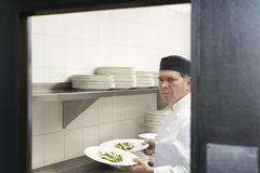 Cuoco unico maschio With Food Plates in cucina Immagini Stock Libere da Diritti