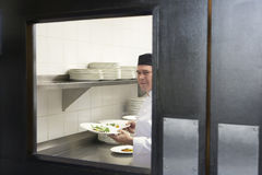 Cuoco unico maschio With Food Plates in cucina Fotografia Stock