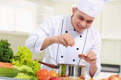 Cuoco unico maschio mentre cucinando immagini stock