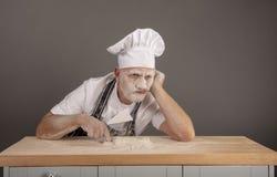 Cuoco unico maturo coperto in farina che sembra infastidita ed alimentata su fotografia stock