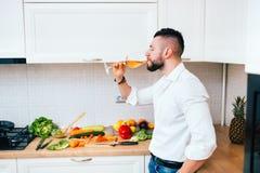 Cuoco unico moderno che prepara insalata per la cena e che beve vino Chiuda sui dettagli di cottura elegante dell'uomo Fotografie Stock Libere da Diritti