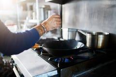 Cuoco unico nella cottura dell'alimento del condimento della cucina del ristorante fotografie stock libere da diritti