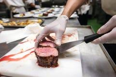 Cuoco unico nella cucina del ristorante o dell'hotel che cucina, sta selezionando il manzo Fotografia Stock Libera da Diritti