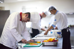 Cuoco unico nelle verdure della fetta della cucina dell'hotel con il coltello Immagini Stock