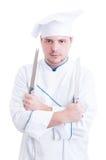 In cuoco unico o in cuoco esperto che tiene due coltelli o lame Fotografia Stock
