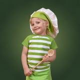 Cuoco unico sorridente del bambino con un grande cucchiaio di legno Fotografie Stock Libere da Diritti