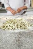 Cuoco unico Standing At Counter con la pasta degli spaghetti Fotografia Stock Libera da Diritti