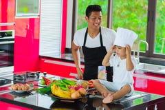 Cuoco unico tailandese privato che cucina, il suo piccolo figlio in cappello s vicina del ` s del cuoco unico immagine stock