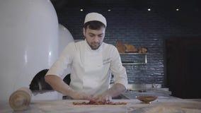 Cuoco unico in uniforme bianca che funziona carne cutted cruda mettente veloce sulla base della pasta che si trova sulla tavola i stock footage