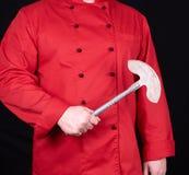 Cuoco unico in uniforme rossa che tiene un vecchio coltello del metallo per carne e le verdure fotografia stock libera da diritti