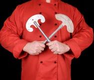 Cuoco unico in uniforme rossa del tessuto che tiene i vecchi coltelli del metallo fotografia stock libera da diritti