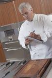 Cuoco unico Writing On Notepad in cucina commerciale Immagini Stock Libere da Diritti