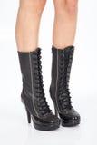 Cuoio nero degli stivali per le donne sulle strade private bianche del fondo Immagini Stock
