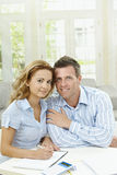 Cuople planning at home. Happy couple sitting at home, planning with paper and calculator Royalty Free Stock Photography