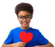 Cuore afroamericano dei biglietti di S. Valentino della tenuta del ragazzo di scuola Fotografia Stock