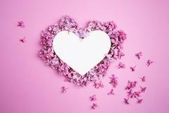 Cuore bianco decorato con i fiori lilla su fondo rosa porpora immagini stock