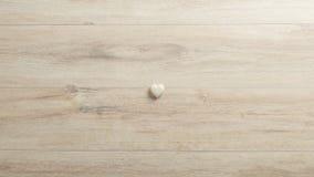 Cuore bianco fatto della pietra che si trova su uno scrittorio del woodenk Immagine Stock