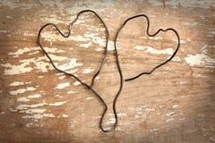 Cuore bifilare su fondo di legno Fotografia Stock Libera da Diritti