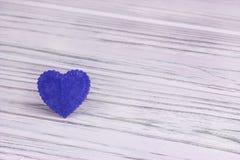 Cuore blu di feltro su un fondo di legno bianco Fotografia Stock
