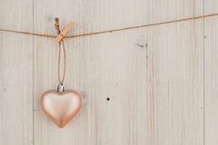 Cuore che appende sulla corda da bucato Sul vecchio tema di giorno di legno background Immagini Stock