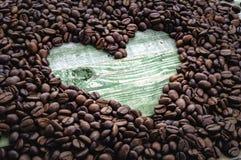 Cuore in chicchi di caffè sulla tavola di legno verde Fotografia Stock
