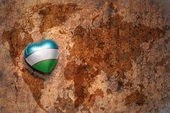 Cuore con la bandiera nazionale dell'Uzbekistan su un fondo d'annata della carta della crepa della mappa di mondo Fotografia Stock