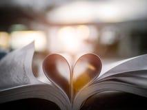 Cuore da una pagina del libro contro un fuoco molle di bello tramonto Fotografie Stock