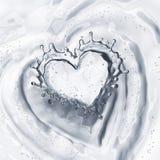 Cuore dalla spruzzata dell'acqua con le bolle su bianco Fotografia Stock