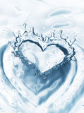 Cuore dalla spruzzata dell'acqua con le bolle sul fondo dell'acqua blu Fotografia Stock Libera da Diritti