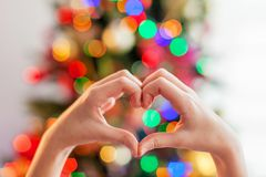 Cuore dalle mani davanti all'albero di Natale immagini stock