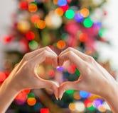 Cuore dalle mani davanti all'albero di Natale fotografia stock