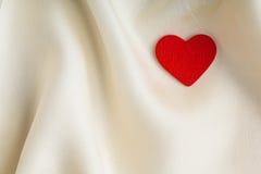 Cuore decorativo di legno rosso su fondo di seta bianco. fotografia stock