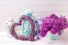 Cuore decorativo, fiori lilla e lanterne del brigh sul wo bianco Immagini Stock Libere da Diritti