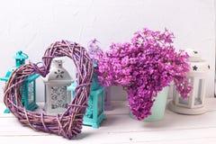 Cuore decorativo, fiori lilla e lanterne del brigh sul wo bianco Immagini Stock